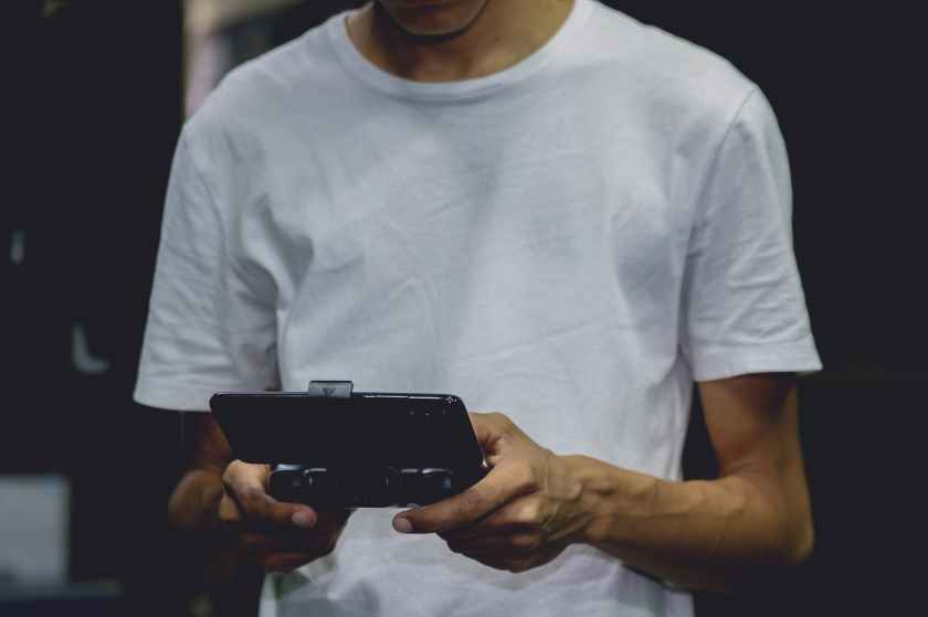 a smartphone game controller on a person s hand